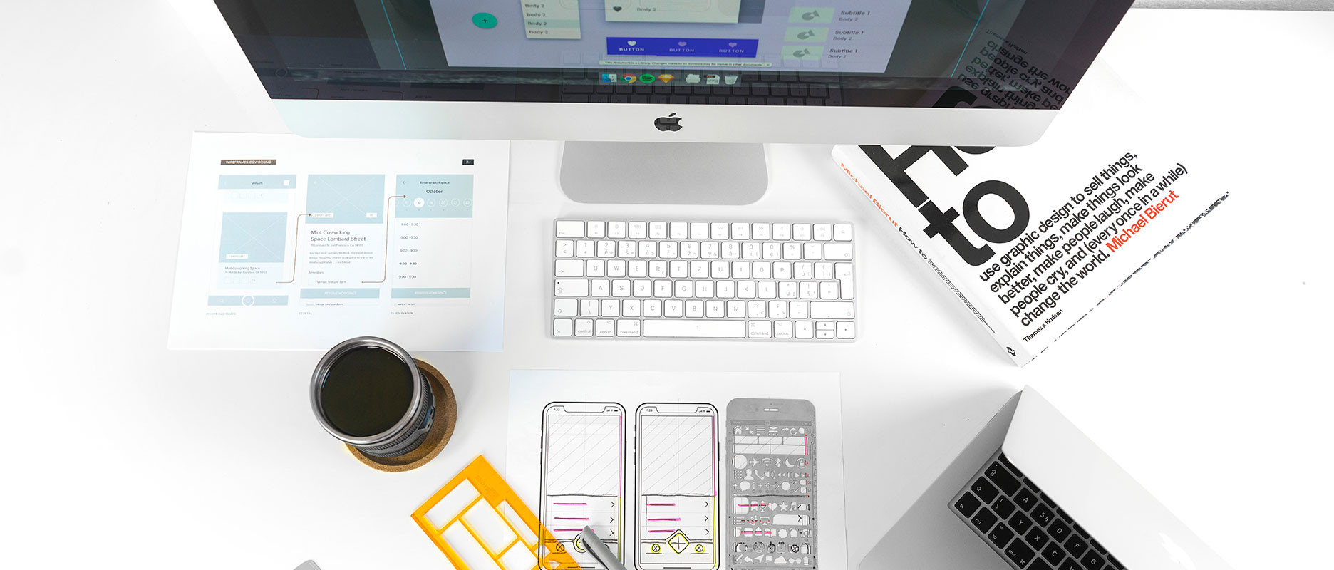 Some design schemes, a book, a cup of coffee and a laptop on a desk
